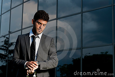 Young businessman looking clock at night