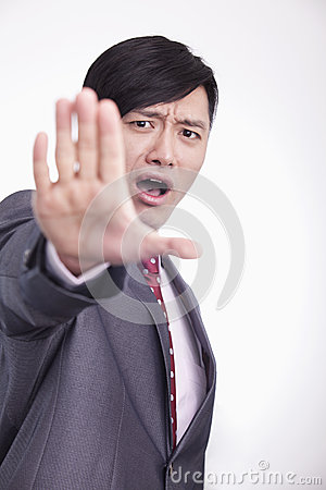 Young businessman with mouth open and hand raised in stop gesture, studio shot
