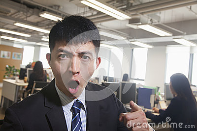 Young Businessman pointing and shouting, looking at camera