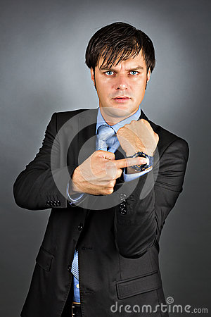 Free Young Businessman Pointing To His Watch With An Angry Expression Stock Photo - 34491680