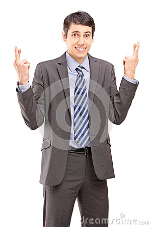 Young businessman posing with fingers crossed for luck