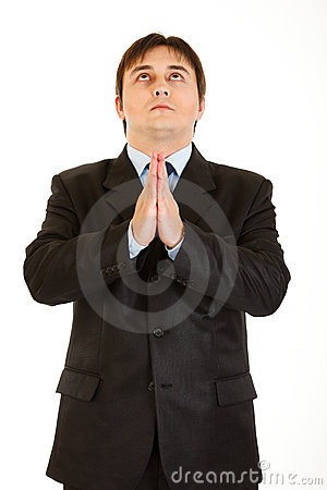 Young businessman praying for success isolated