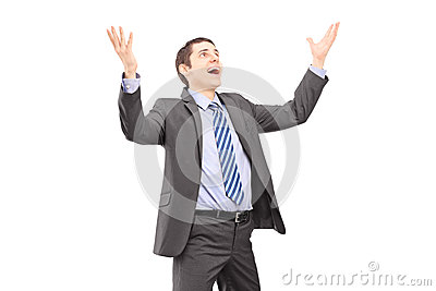 Young businessman with raised hands waiting something to fall