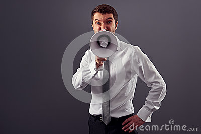 Young businessman screaming in megaphone