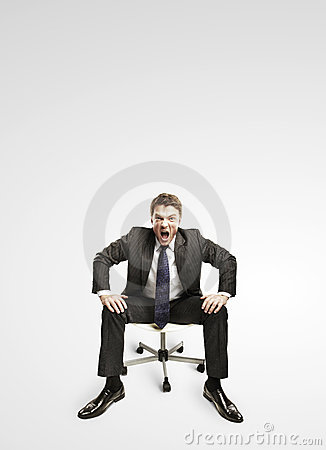 Young businessman shouting and sitting on a chair.