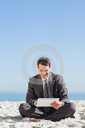 Young businessman siiting using his tablet computer