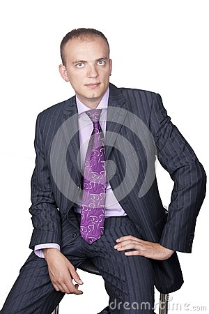 Young businessman sitting against isolated