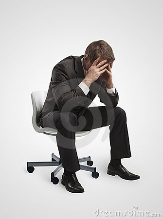 Young businessman sitting on chair with head down