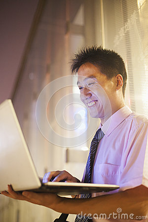 Young businessman smiling and looking at his laptop outdoors at night