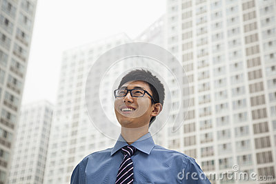 Young businessman smiling and looking at the sky, outdoors