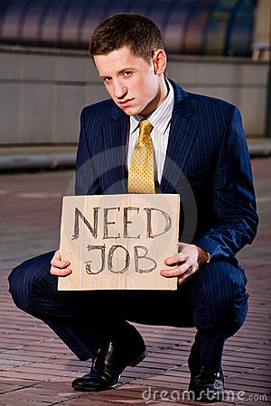 Young businessman squatting with sign Need Job