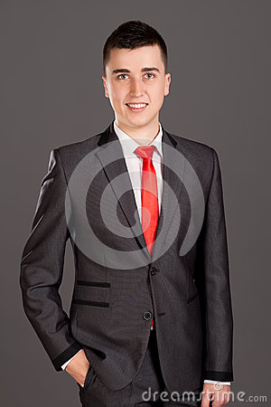 Young businessman standing on grey background
