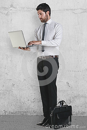 Young businessman standing with laptop and briefcase.