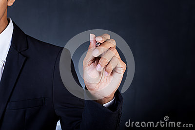 Young businessman in suit holding pen
