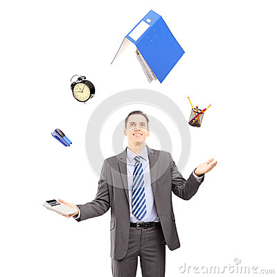 Young businessman in a suit juggling with office supplies