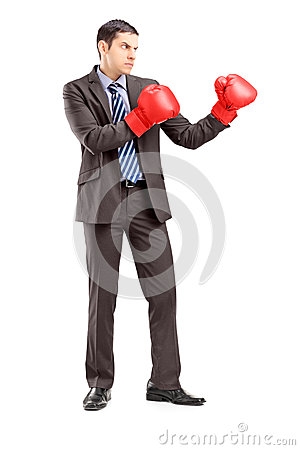 Young businessman in suit with red boxing gloves