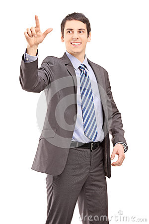Young businessman touching something imaginery