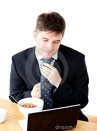 Young businessman using laptop during breakfast