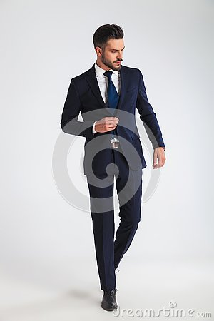 Free Young Businessman Walking And Buttoning His Navy Suit Royalty Free Stock Images - 125240609