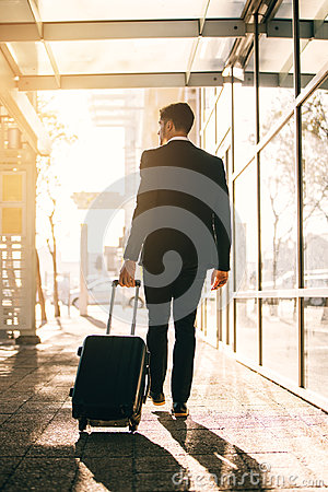 Free Young Businessman Walking With Suitcase Outside Airport Building Royalty Free Stock Photos - 97080228