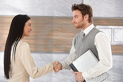 Young businesspeople greeting each other smiling Stock Photo