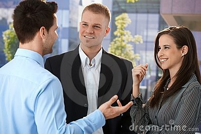 Young businesspeople talking outside of office