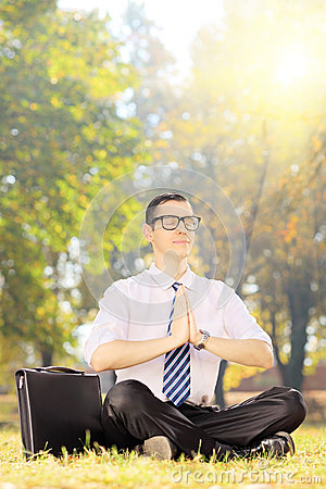 Young businessperson doing yoga seated on a grass in a park