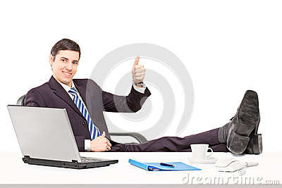 Young businessperson sitting on a chair with his legs up and giv