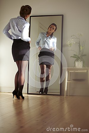 Young businesswoman checking herself in the mirror