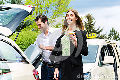 Young businesswoman in front of taxi