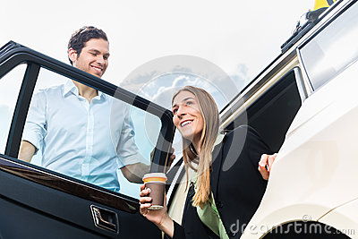 Young businesswoman getting out of taxi
