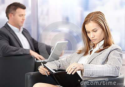 Young businesswoman looking at organizer