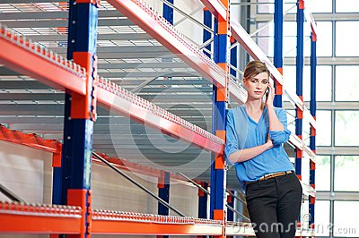 Young businesswoman on mobile phone in warehouse