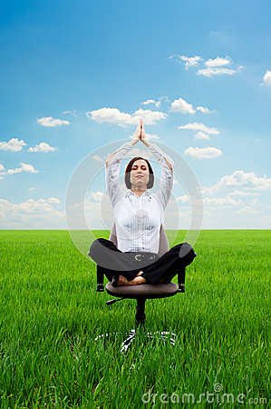 Young businesswoman practicing yoga on the meadow