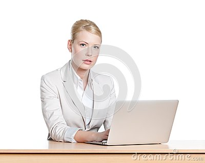 Young businesswoman sitting with laptop, isloated