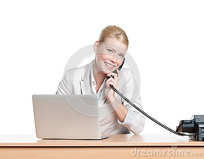 Young businesswoman sitting at a office table and talking by phone