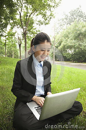 Young businesswoman sitting in the park and working on her laptop