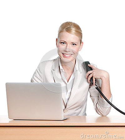 Young businesswoman sitting with phone handset