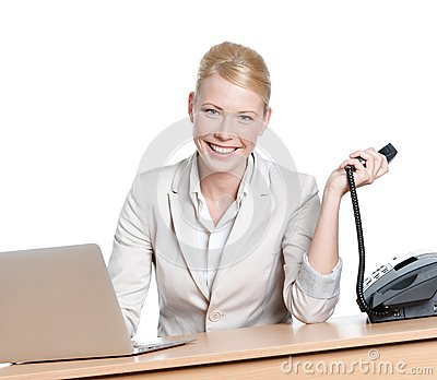 Young businesswoman sitting at a table with phone