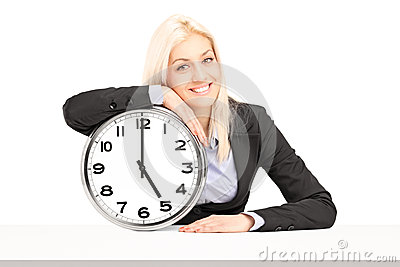 Young businesswoman sitting with a wall clock