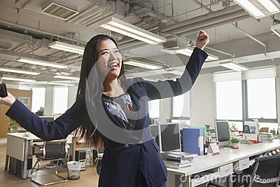 Young businesswoman smiling with arms raised in the office