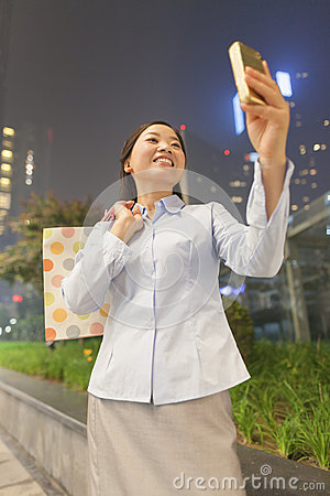 Young businesswoman smiling and taking a picture of herself with her cell phone