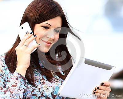 Young businesswoman talking digital tablet and mobile phone
