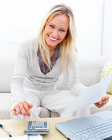 Young businesswoman using calculator at home