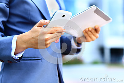Young businesswoman using digital tablet and mobile phone
