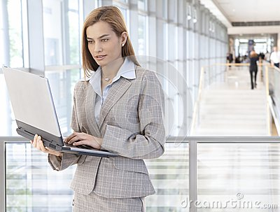 Businesswoman using laptop in office lobby