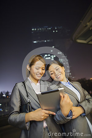 Young businesswomen looking at digital tablet and walking