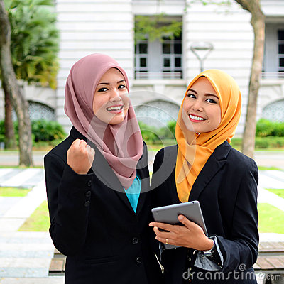 Young businesswomen sharing info on laptop Stock Photo