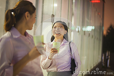 Young businesswomen smiling and drinking coffee outdoors at night