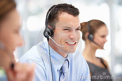Young call centre operator helping customer